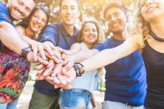 Grupp av vänner med händer på bunt royaltyfria foton