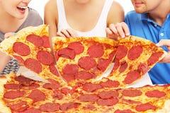 Grupp av vänner med pizza Arkivbild