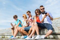 Grupp av vänner med smartphonen utomhus royaltyfri foto