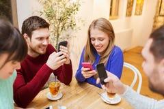 Grupp av vänner med smartphones som möter på kafét Arkivfoton