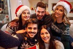Grupp av vänner med tomtebloss som tycker om i parti på jul D Royaltyfria Bilder
