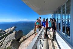 Grupp av vänner på alpint kojadäck royaltyfria bilder