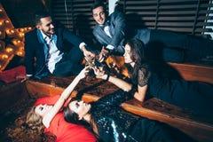 Grupp av vänner på klubban som ligger på golvet och jublen efter medeltal royaltyfri fotografi