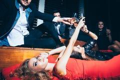 Grupp av vänner på klubban som ligger på golvet och jublen efter medeltal royaltyfria foton