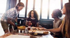 Grupp av vänner på pizzarestaurangen royaltyfri bild