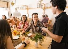 Grupp av vänner på restaurangen arkivbild