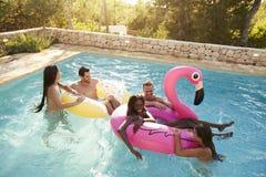 Grupp av vänner på semester som kopplar av i utomhus- pöl royaltyfri bild