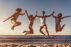 Grupp av vänner på stranden arkivfoto