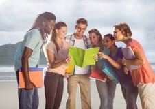 Grupp av vänner på stranden med böcker fotografering för bildbyråer