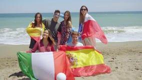 Grupp av vänner på stranden med fotboll och flaggor arkivfilmer