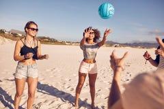 Grupp av vänner på stranden som spelar volleyboll Royaltyfri Foto
