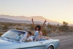 Grupp av vänner på vägturen som kör den klassiska konvertibla bilen arkivbilder