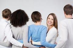 Grupp av vänner som anknyter armar som bort vänder mot fotografering för bildbyråer