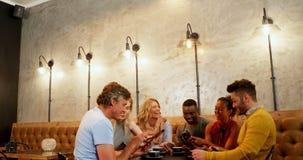 Grupp av vänner som använder mobilen, medan ha kaffe 4K 4k arkivfilmer