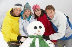 Grupp av vänner som bygger snowmanen royaltyfri foto