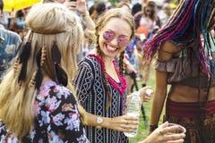 Grupp av vänner som dricker öl som tillsammans tycker om musikfestival Arkivfoto