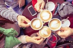 Grupp av vänner som dricker cappuccino på cafeteriarestaurangen Arkivbild