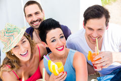 Grupp av vänner som dricker coctailar i strandstång Arkivfoton