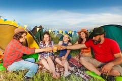 Grupp av vänner som dricker utanför deras tält royaltyfria bilder