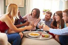 Grupp av vänner som firar med ett hemmastatt rostat bröd royaltyfri foto