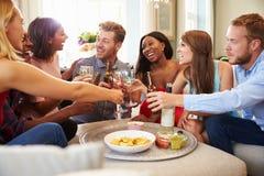 Grupp av vänner som firar med ett hemmastatt rostat bröd arkivbilder