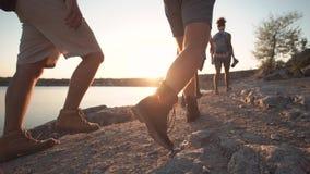 Grupp av vänner som fotvandrar på den steniga kustlinjen royaltyfri foto