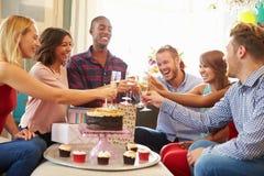 Grupp av vänner som gör ett rostat bröd för att fira födelsedag fotografering för bildbyråer