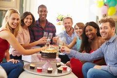 Grupp av vänner som gör ett rostat bröd för att fira födelsedag royaltyfri bild