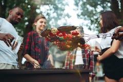 Grupp av vänner som gör grillfesten i trädgården begrepp om bra och positivt lynne med vänner arkivbilder