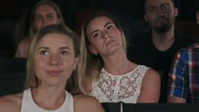 Grupp av vänner som håller ögonen på en film på bioteatern och applåderar på slutet arkivfilmer