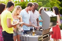 Grupp av vänner som har den utomhus- grillfesten hemma Arkivfoton