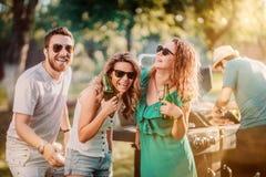 Grupp av vänner som har drinkar och lagar mat på grillfestpartiet royaltyfria bilder