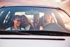 Grupp av vänner som har gyckel i bilen royaltyfria bilder