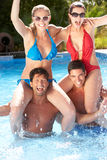 Grupp av vänner som har gyckel i simbassäng Royaltyfria Foton