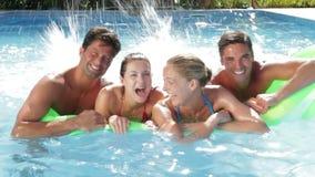 Grupp av vänner som har gyckel i simbassäng tillsammans lager videofilmer