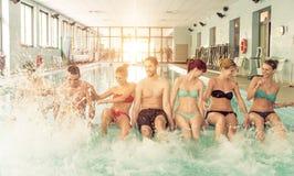 Grupp av vänner som har gyckel i simbassängen Royaltyfri Fotografi
