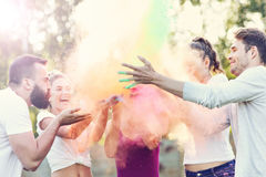 Grupp av vänner som har gyckel på färgfestivalen Royaltyfria Bilder