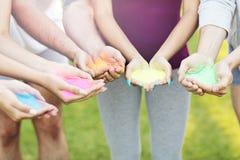 Grupp av vänner som har gyckel på färgfestivalen Arkivbild