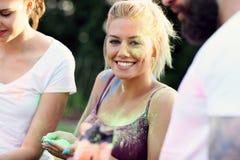 Grupp av vänner som har gyckel på färgfestivalen Royaltyfria Foton