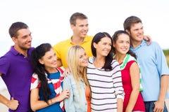 Grupp av vänner som har gyckel på stranden Royaltyfria Bilder