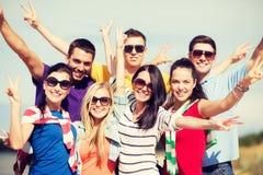 Grupp av vänner som har gyckel på stranden Arkivfoton