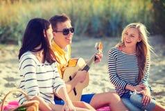 Grupp av vänner som har gyckel på stranden Royaltyfri Bild