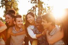 Grupp av vänner som har gyckel tillsammans utomhus Arkivbild