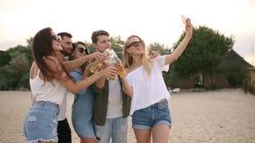 Grupp av vänner som har gyckel som tycker om en dryck och kopplar av på stranden på solnedgången i ultrarapid Unga manar och kvin arkivfilmer