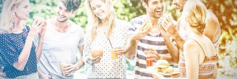 Grupp av vänner som har hamburgare och fruktsaft royaltyfri bild