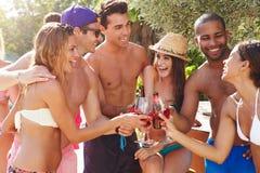 Grupp av vänner som har partiet av simbassängen Fotografering för Bildbyråer