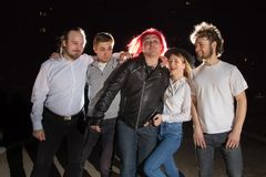 Grupp av vänner som har utomhus- gyckel tillsammans i en natt och ett ljus bakom Royaltyfri Foto