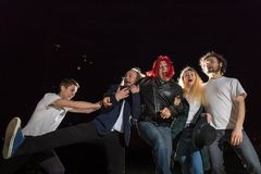 Grupp av vänner som har utomhus- gyckel tillsammans i en natt och ett ljus bakom Arkivbilder