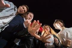 Grupp av vänner som har utomhus- gyckel tillsammans i en natt och ett ljus bakom Fotografering för Bildbyråer