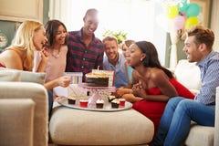 Grupp av vänner som hemma firar födelsedag tillsammans royaltyfria foton